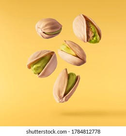 Flying in air fresh raw whole and cracked pistachios  isolated on yellow background. High resolution image