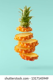 Flying in air fresh ripe Pineapple slices  isolated on pastel turquoise background. High resolution image