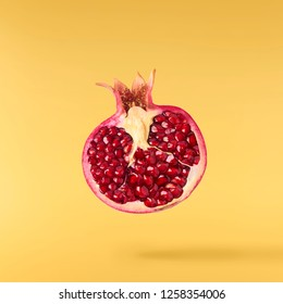 Flying in air fresh ripe pomegranate isolated on yellow background. High resolution image