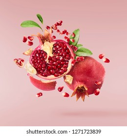 Flying in air fresh ripe whole and cut pomegranate with seeds and leaves isolated on pastel pink background. High resolution image