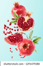 Flying in air fresh ripe whole and cut pomegranate with seeds and leaves isolated on blue background. High resolution image