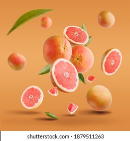 Flying in air fresh ripe whole and cut grapefruit with seeds and leaves isolated on red background. - Shutterstock ID 1879511263
