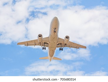 Flying airplane from below - landing / departure - blue sky with clouds