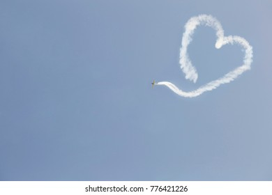 A flying airplane with smoke in the form of a heart.