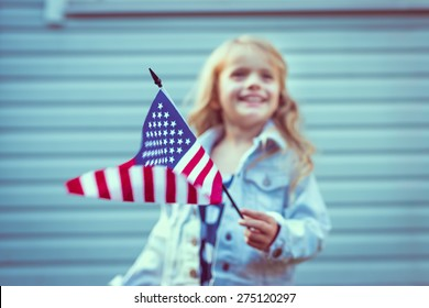 Flying american flag in little girl's hand. Selective focus, blurred background. Independence Day, Flag Day concept. Vintage and retro toning. Instagram filters