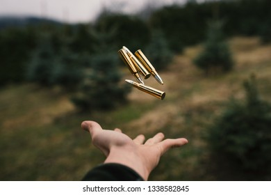 Flying ammunition above a man hand. Professional hunter and ammunition for hunting. Caliber 8x57. Concept of industry.