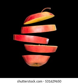 Flying apple. Sliced red apple isolated on black background. Levity fruit floating in the air.