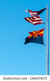 Flying Arizona state and USA flags on the flagpole against blue sky background