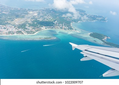 Flying away from Ko Samui through plane window tropical island and sea below.