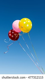Flying balloons with polka dot on the background of blue sky
