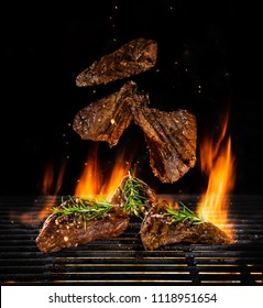 Flying beef steaks on grill with Fire flames. Isolated on black background. Barbecue and grilling. Very high resolution image