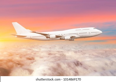 Flying bid double decker airplane above the clouds horizon sky with bright sunset colors