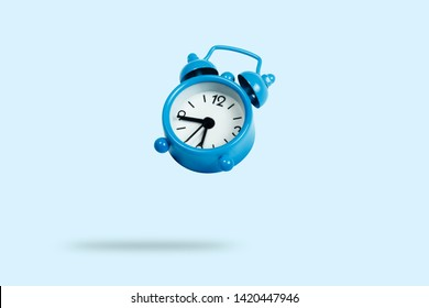 Flying blue alarm clock on a blue background. Levitation