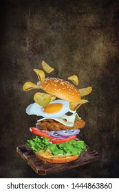 Flying burger with chips and egg on dark background. Copy space text concept poster.