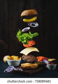 Flying burger ingredients above wooden cutting board. Concept of low gravity motion and meal preparation. Fastfood