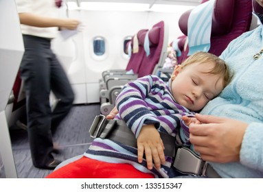 Flying with children. Mother and sleeping two year old baby girl travel on a commercial airliner