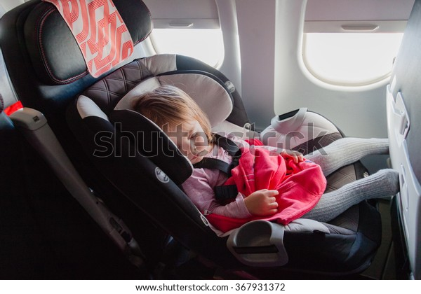 Flying with children: two year old baby sleeping in her own car seat setting on an ordinary seat on a commercial airliner. Concept photo of air travel with baby. Natural in-plane lightning conditions