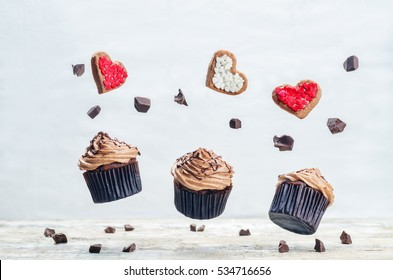 Flying chocolate cupcakes and cookies in the forms of heart. toning. selective focus