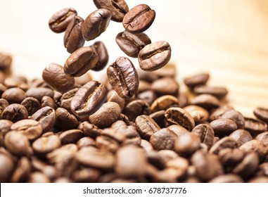 Flying coffee beans. Coffee beans are falling on pile isolated on a white background