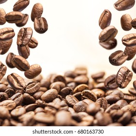 Flying coffee beans. Coffee beans are falling on a pile isolated on a white background