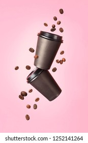 Flying coffee from a paper cups with flying coffee beans on a pink background. Coffee concept. Mock up.  Empty polystyrene coffee drinking mug mockup front view. Clear plain tea take away package.
