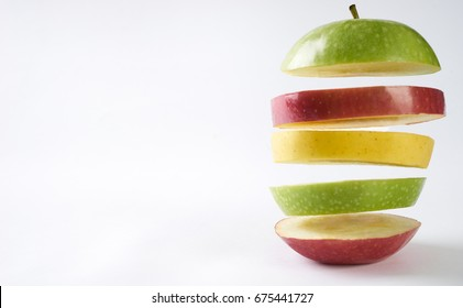 Flying colorful apples. Sliced red apple green apple and yellow apple isolated on white background with copy space. Levity raw fruit floating in the air. Healthy food and detox concept.