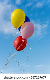 Flying colorful balloons against blue sky
