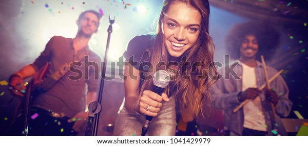 Flying colors against portrait of singer with musicians on stage at nightclub