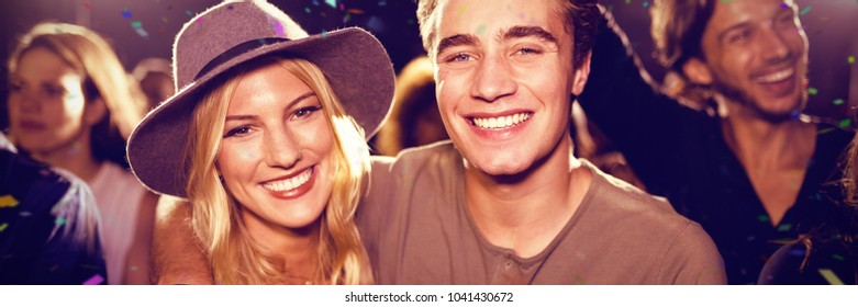 Flying colors against portrait of smiling friends standing at nightclub