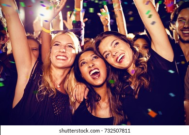 Flying colours against cheerful female friends enjoying at music festival