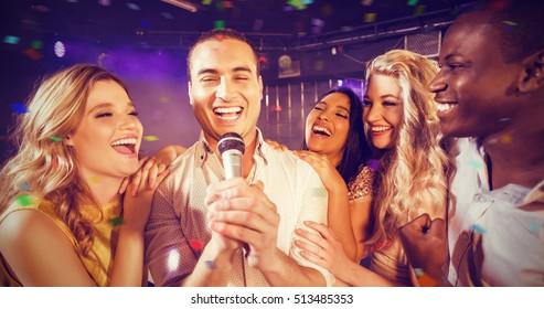 Flying colours against happy friends singing at karaoke