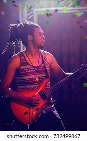 Flying colours against male guitarist performing at nightclub