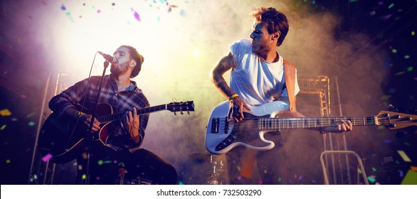 Flying colours against male guitarists performing on stage