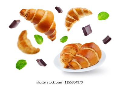 Flying croissants with chocolate and mint leaves isolated. toning. selective focus