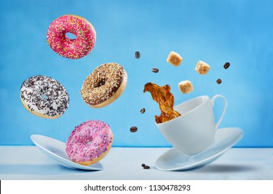 Flying cup of coffee with multicolored donuts on a blue background. toning. selective focus