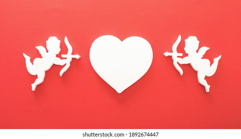 Flying cupid silhouette with hearts, gifts, happy Valentine's Day banners, paper art style. Amour on red paper