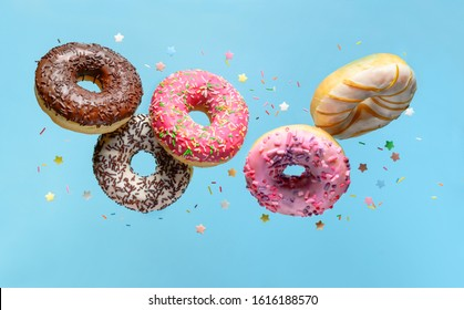 Flying donuts. Mix of multicolored doughnuts with sprinkles on blue background.
