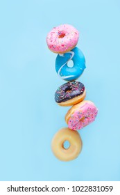 flying doughnuts - balancing tower of multicolored sweet donuts with sprinkles on blue background