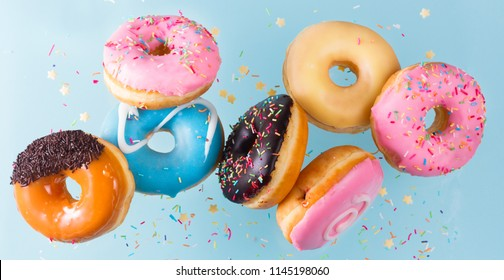 flying doughnuts scene - mix of multicolored sweet donuts with sprinkel on blue background