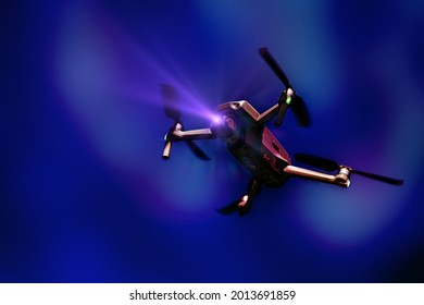 A flying drone. Airborne quadcopter. Also known as a drone or UAV, Unmanned Aerial Vehicle. Drone with camera on a colorful background with copy space.