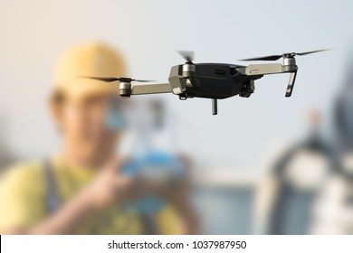 flying drone with blurred controller in background
