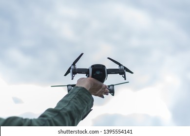 Flying drone in a female hand against the sky.