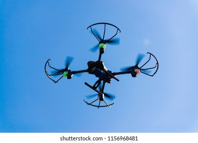 Flying drone or quad copter in clear blue sky