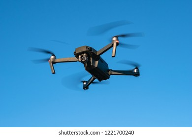 Flying drone or quadcopter with camera at blue sky background, close up