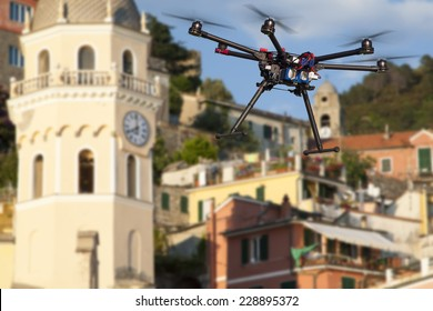 A flying drone without a camera with a blured old town in the background.