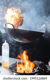 Flying flambe noodles for wok box with meat, soy sauce fried in a wok pan, street food.