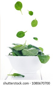 Flying food spinach leaves in bowl on white, floating food summer concept