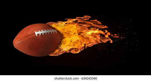 Flying football engulfed in trailing flames with sparks flying on a black background. Concept of a fiery competition or fast moving ball.
