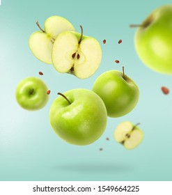 Flying fresh green apple with seeds on blue background. Creative levitation food, summer fruits