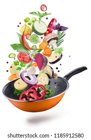 Flying fresh vegetables and spices over a pan. File contains clipping path. Flying motion effect.